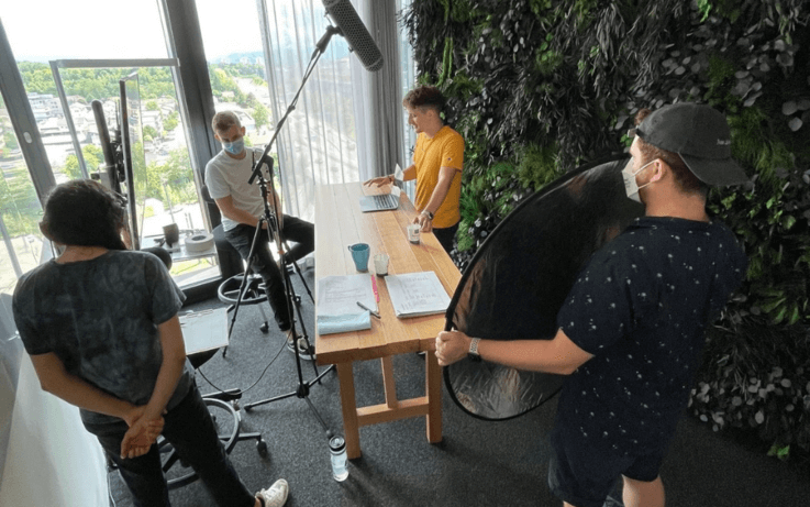Four men filming a video around large wooden table