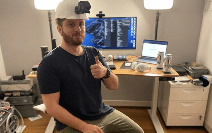 man sitting with safety hat and camera on forehead with desk and screens in the background