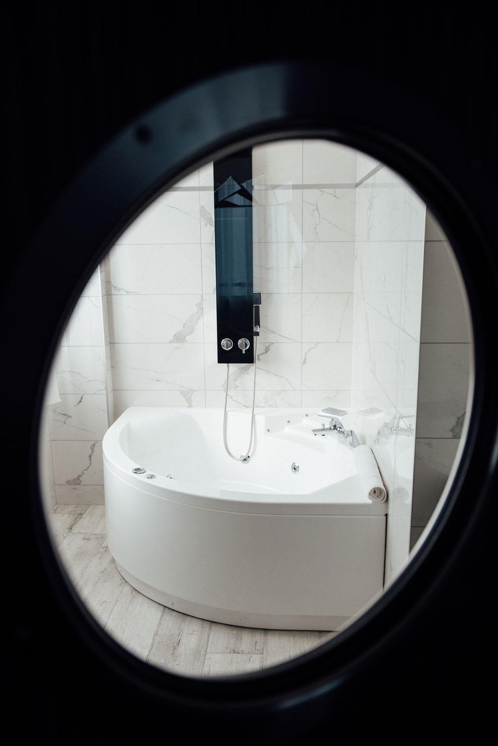 Salle de bain, baignoire balnéothérapie jacuzzi vue à travers un hublot | Amirauté Hôtel La Baule