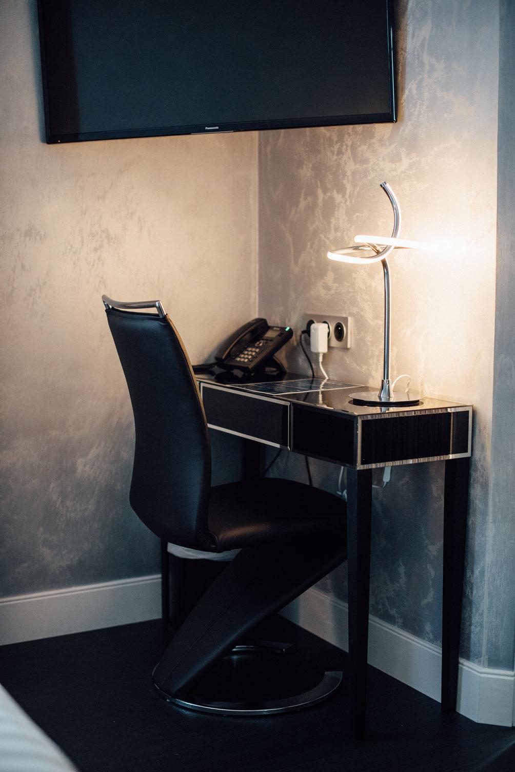 Table, chaise, lampe de chevet, téléphone et prises electriques | Amirauté Hôtel La Baule