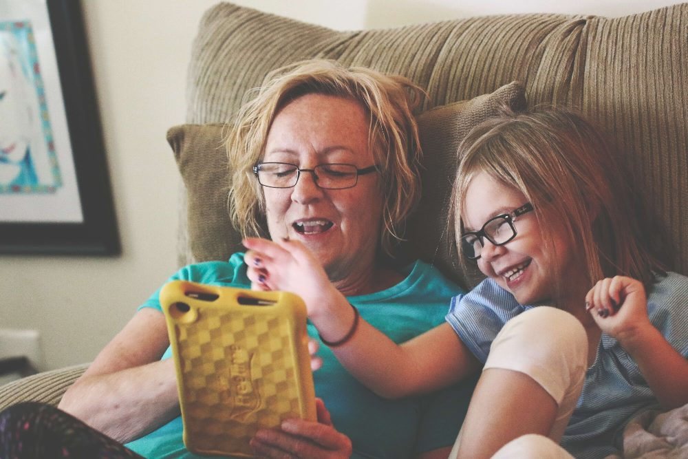 mother and daughter playing on tablet