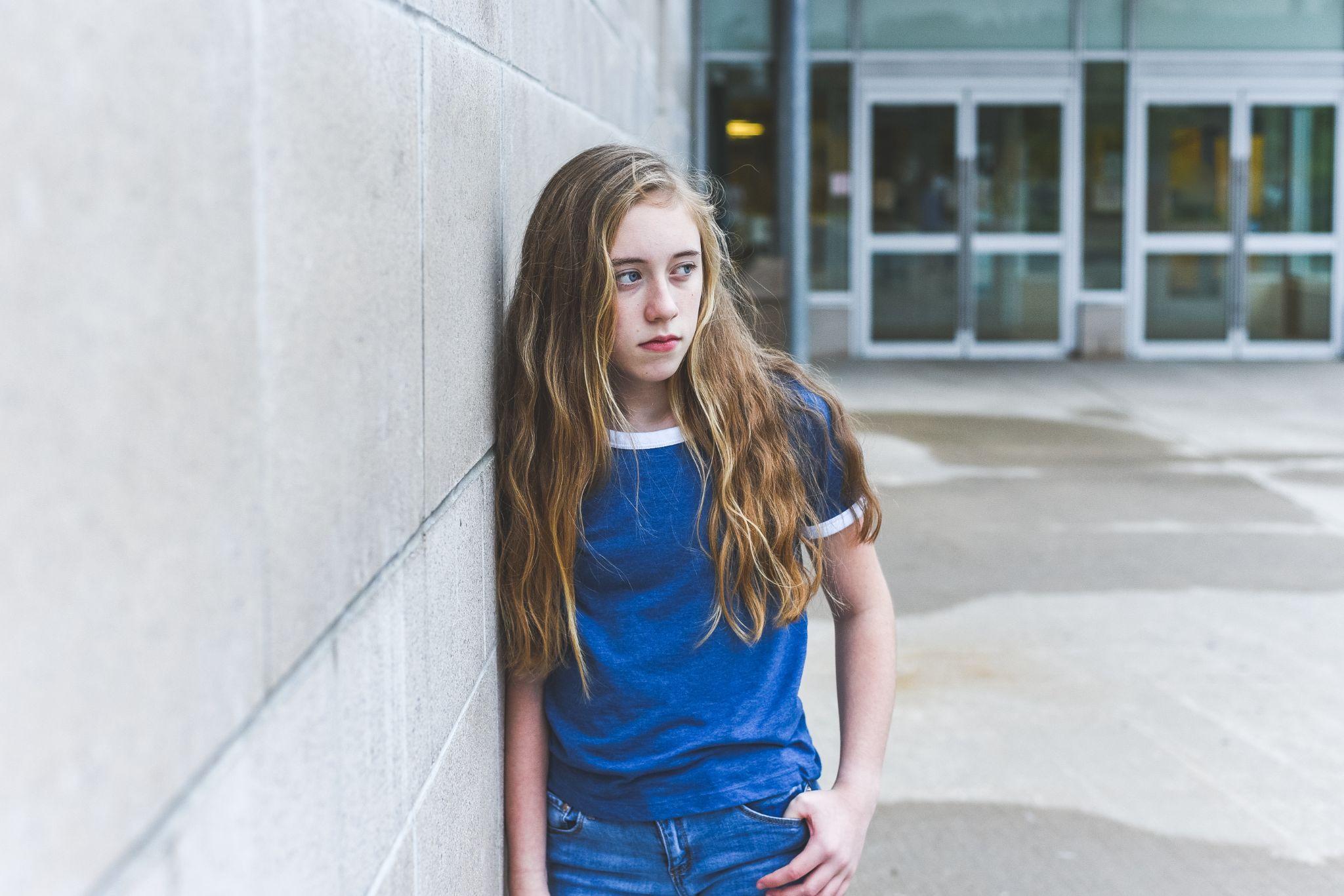 Sad teenage girl leaning against brick wall