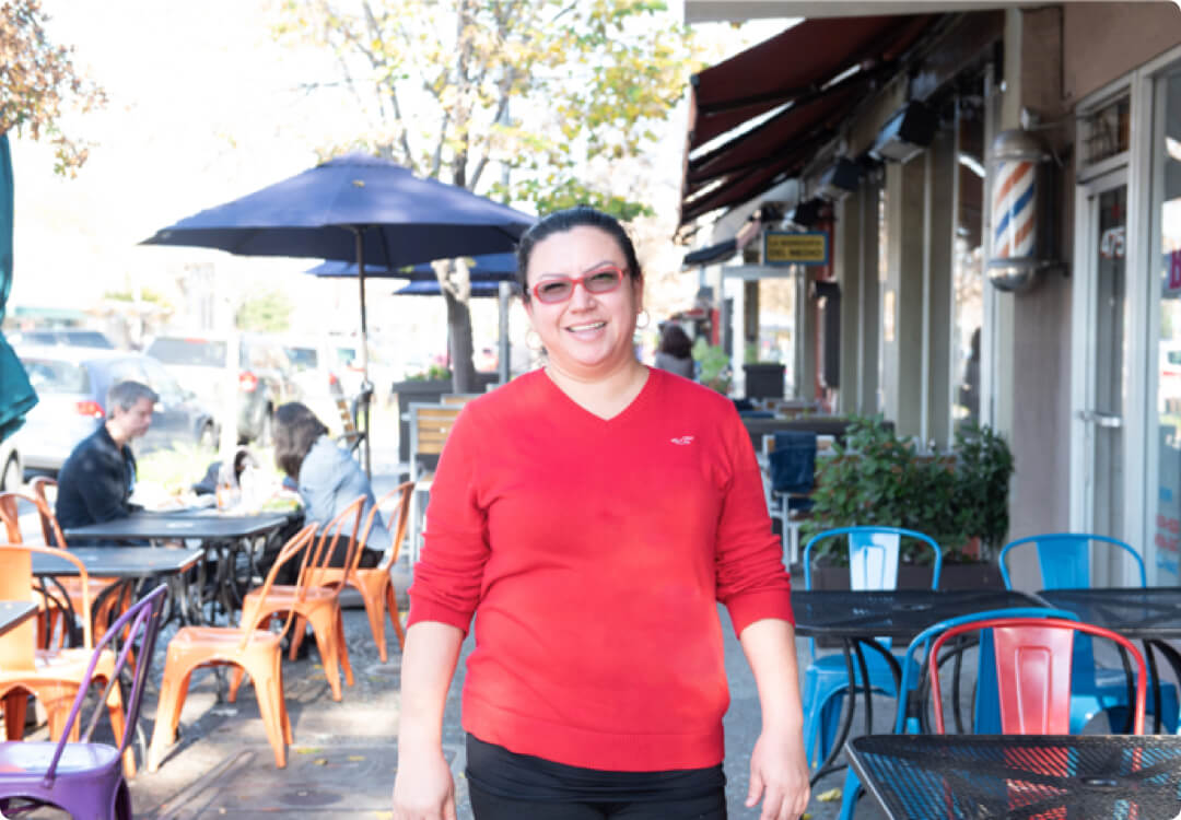 Hourly customer Maria Moya from Izzy's Brooklyn Bagels smiling outside the restaurant.