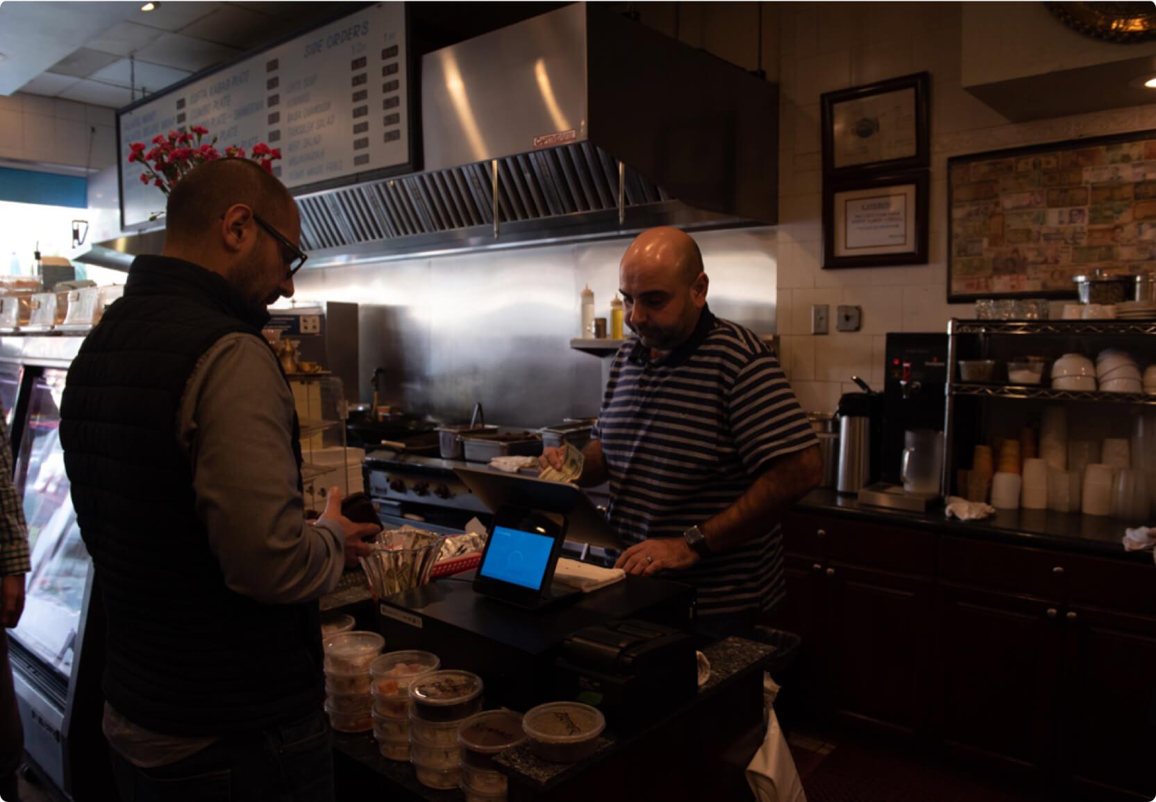 Hourly customers Bader Khalil of Mediterranean Wraps on their cash register.