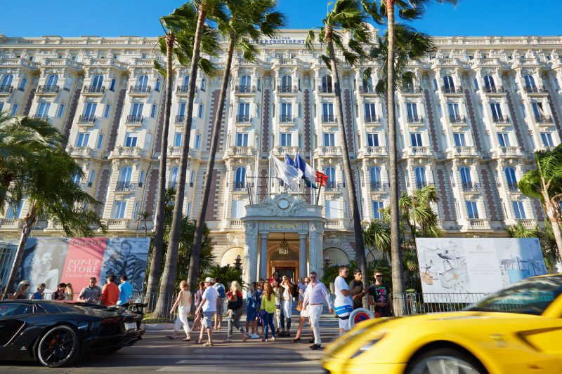 cannes, people walking and luxury cars in front of hotel intercontinental carlton
