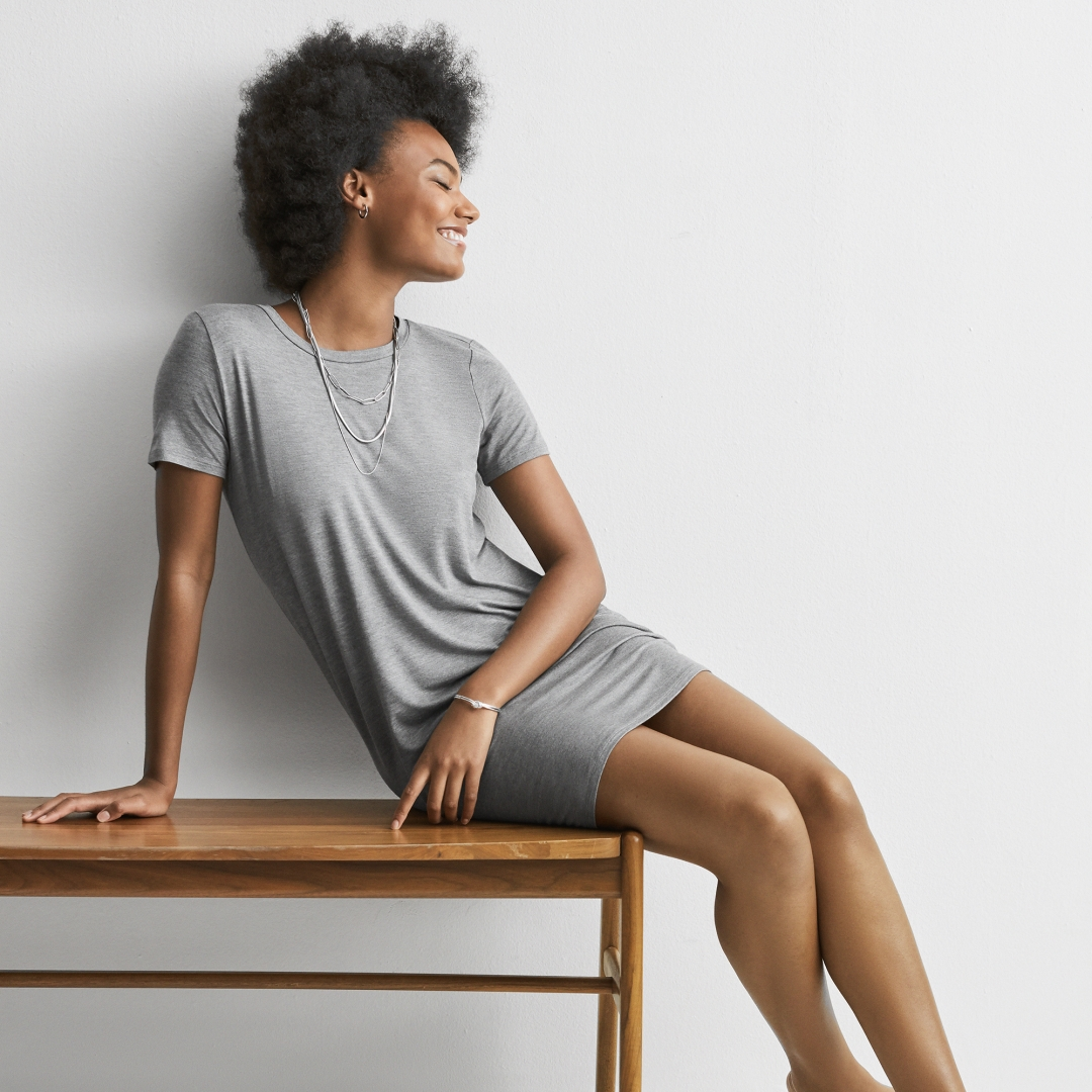model with small afro sitting on a bench facing right smiling leaning against her arm wearing silver necklace stack and great tshirt dress from Express
