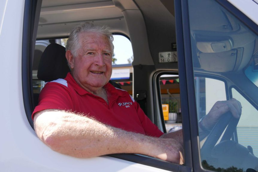 Mal Rixon sits in the drivers seat of the mini bus wearing a red shirt. His elbow is resting on the window
