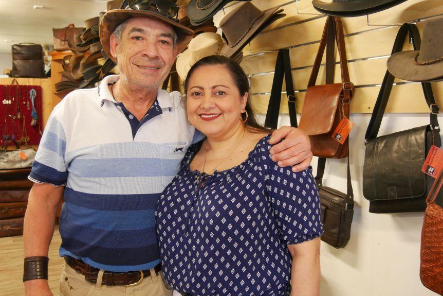 A couple with their arm around each other. There are a rack of hats lining the walls in the background.
