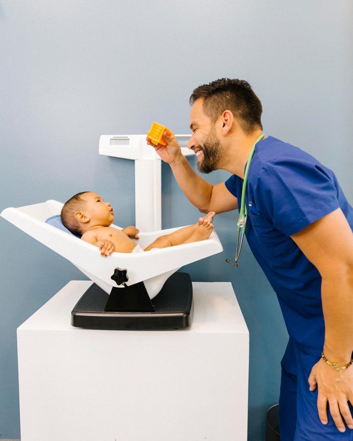 Pediatra pesando a bebé