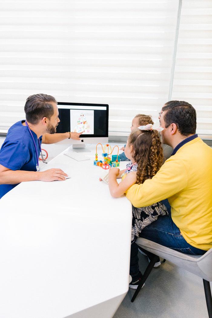 Pediatra mostrando pirámide nutricional a familia y pacientes