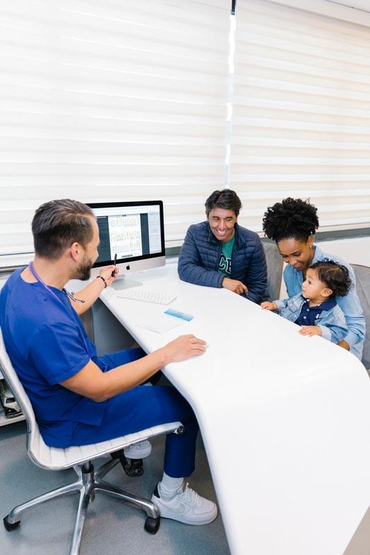 Pediatra funcional atendiendo a familia y paciente en el consultorio