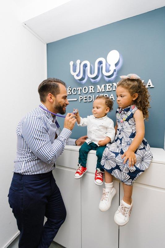 pediatra sonriendo junto a sus pacientes