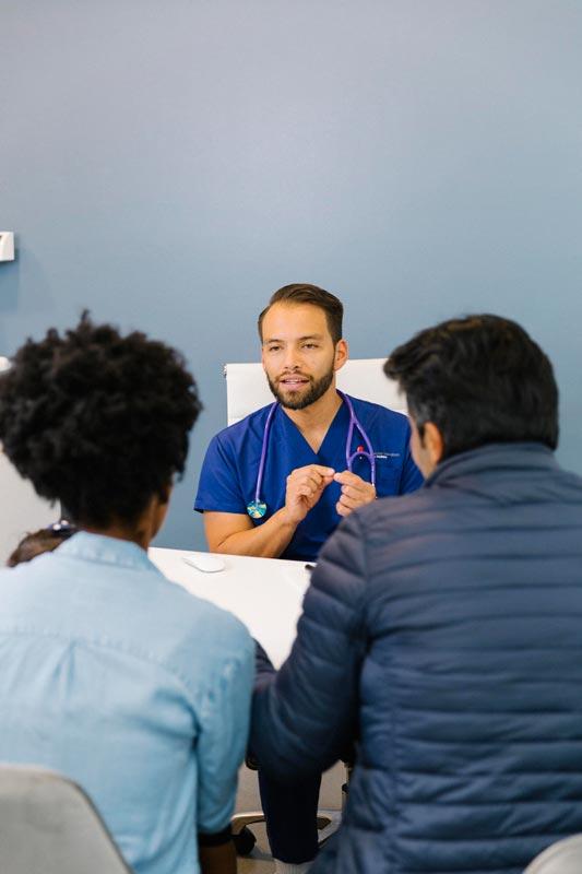 Pediatra en su consultorio hablado con los padres de su paciente