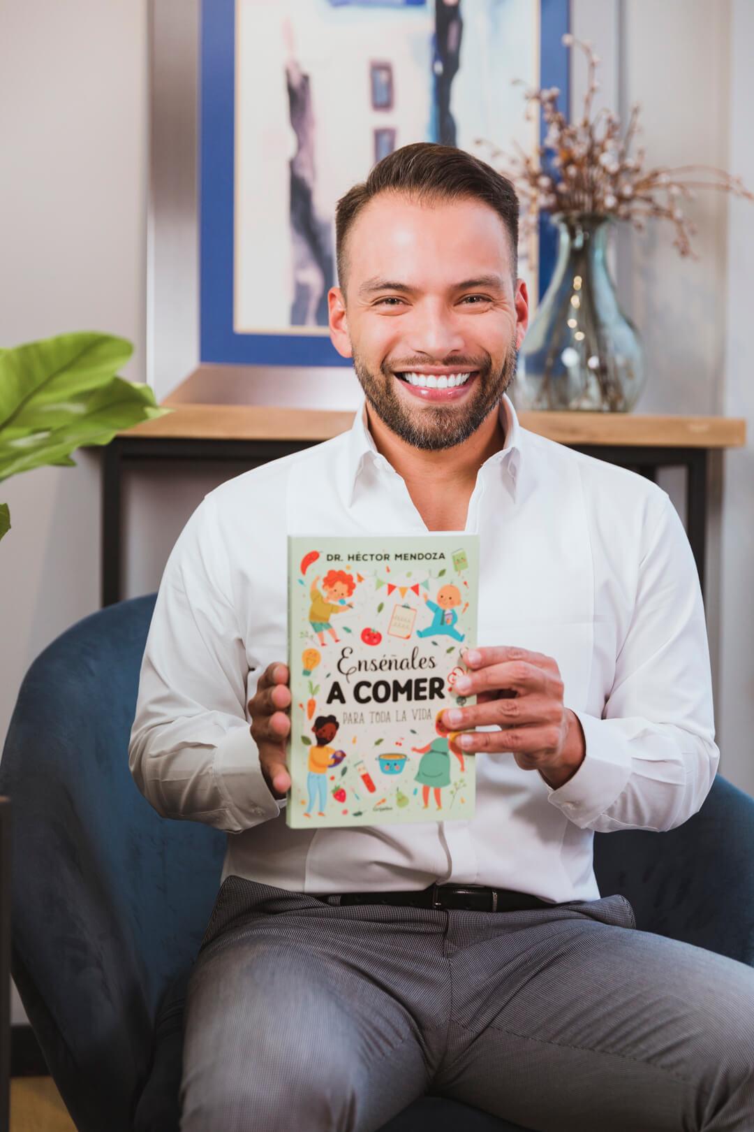 Doctor Hector Mendoza mostrando su libro Enséñales a comer para toda la vida