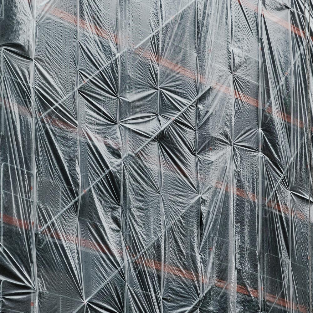 Artistic photo of dark coloured plastic stretched across a building in construction.