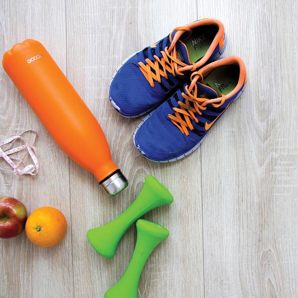 Still life photo of some workout gear and fruit on the floor.