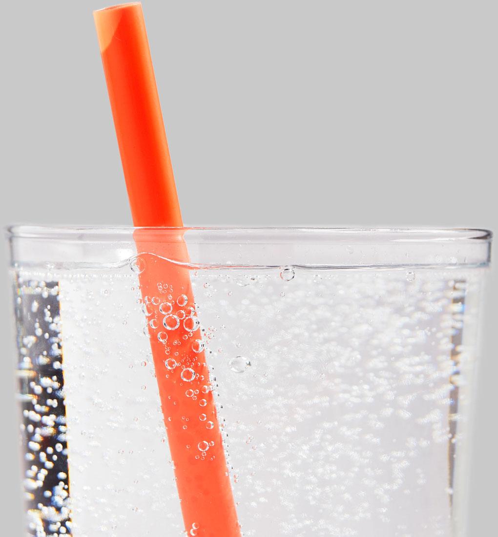 Closeup photo of water glass with orange ECLIPSE™ Straw.