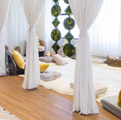 A cozy location with a wooden floor, plants, cushions, and white curtains.
