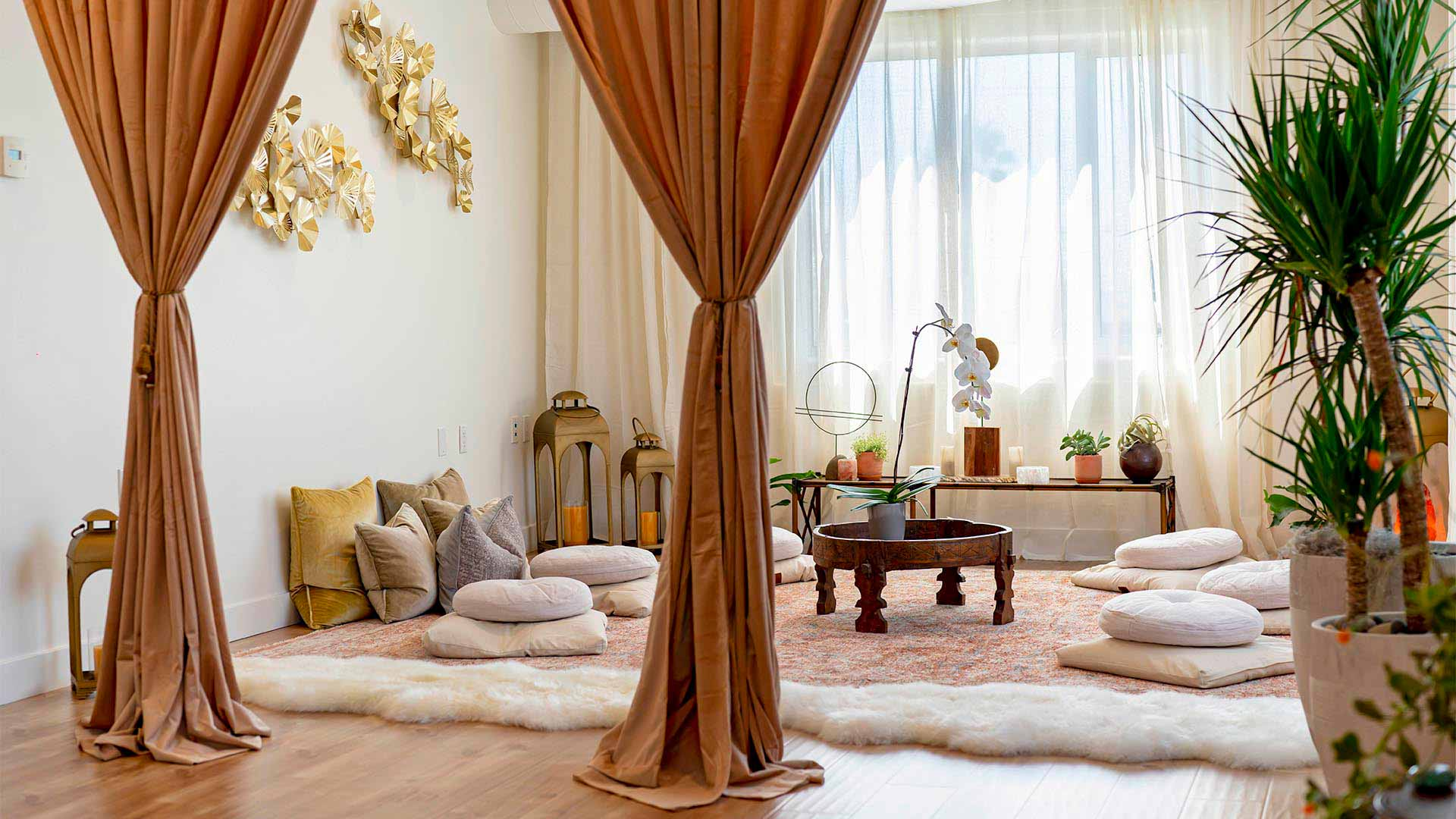 A cozy open room with wooden floor, plants, soft cushions and velvet curtains.