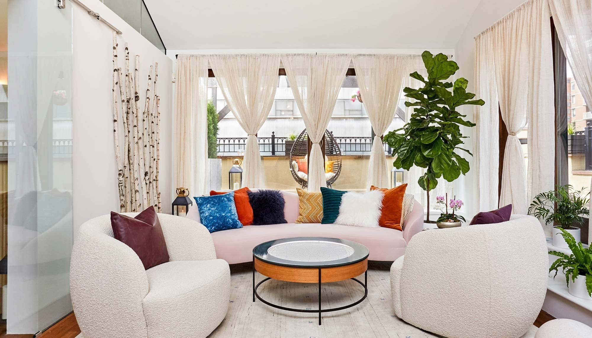 A cozy location with white couches, colorful cushions, plants, and curtains.