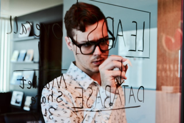 man with glasses writing on a glass board
