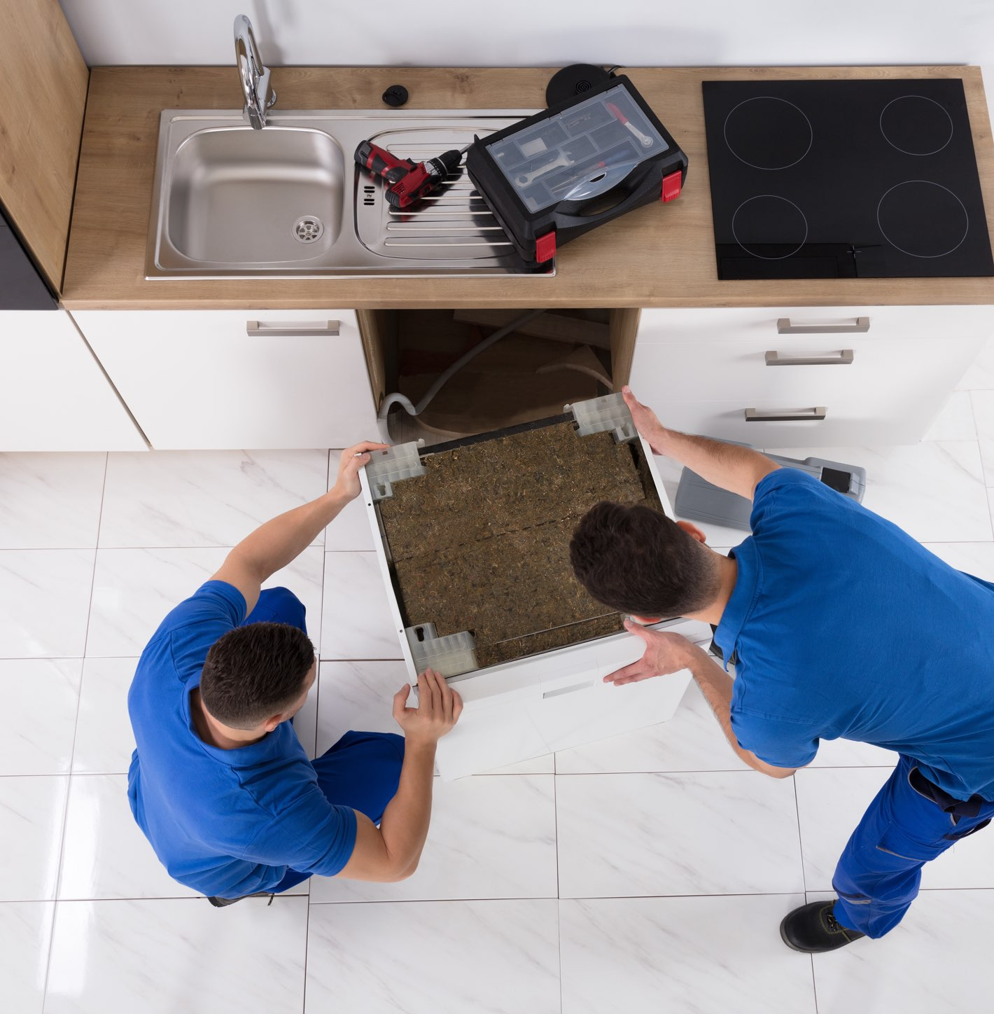Two male workers in blue uniforms installing a dishwasher in a home