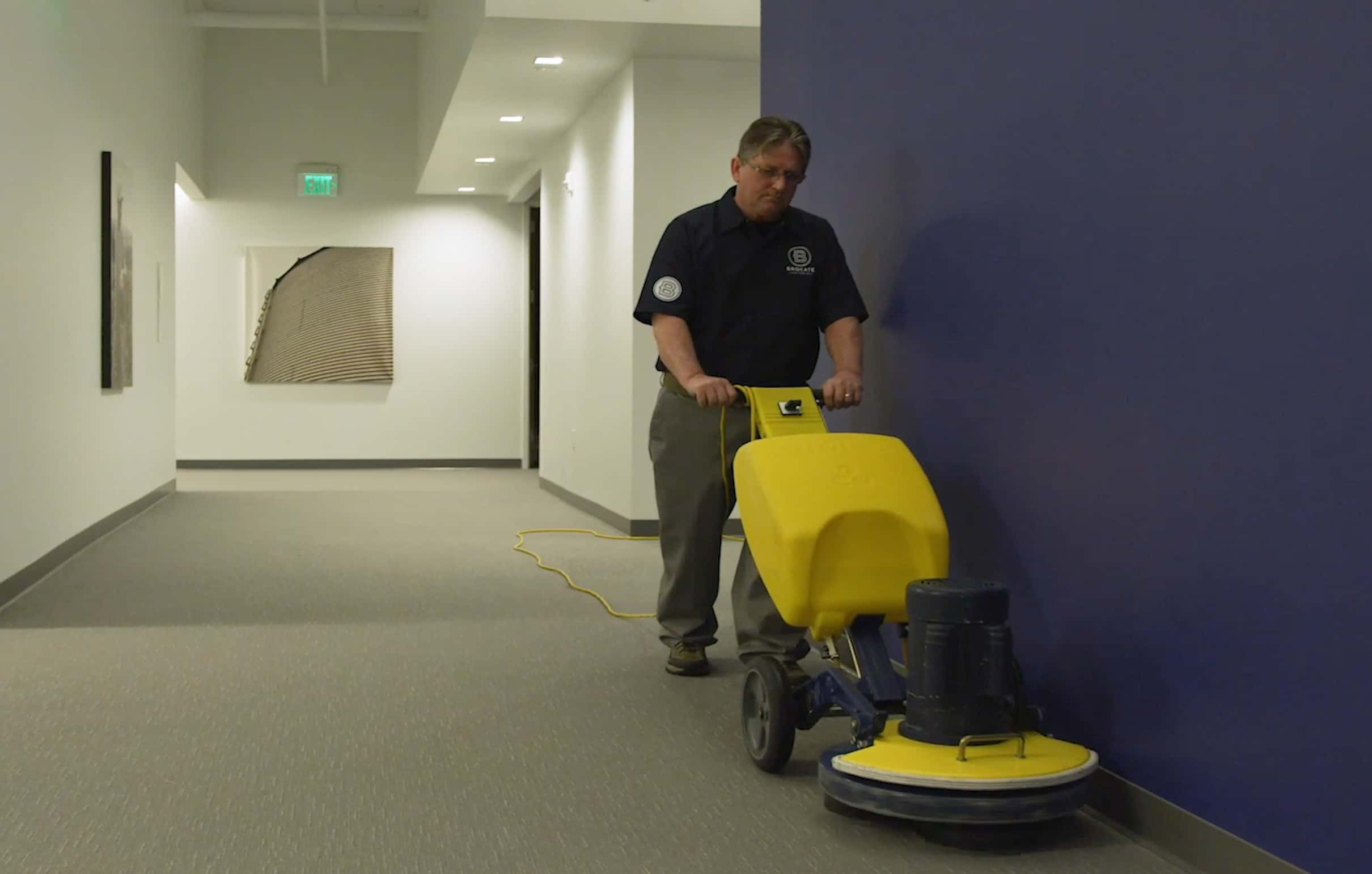 Brokate janitor using a carpet cleaning machine to clean a minimalist office