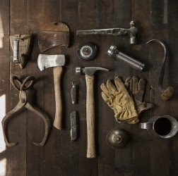 Several antique tools, a pair of gloves, and a cup of coffee lying on a wood table
