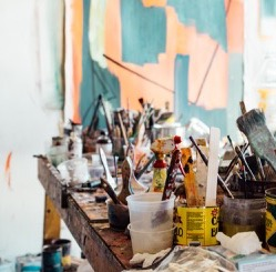 Paint brushes and cans sitting atop a paint-splattered table with a painting in the background