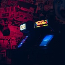 Two arcade games– Frogger and Pac Man– sitting side by side in a dark room with posters covering the wall