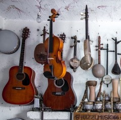 Many musical instruments hanging on a while including two acoustic guitars, one viola, and a various middle eastern stringed instruments