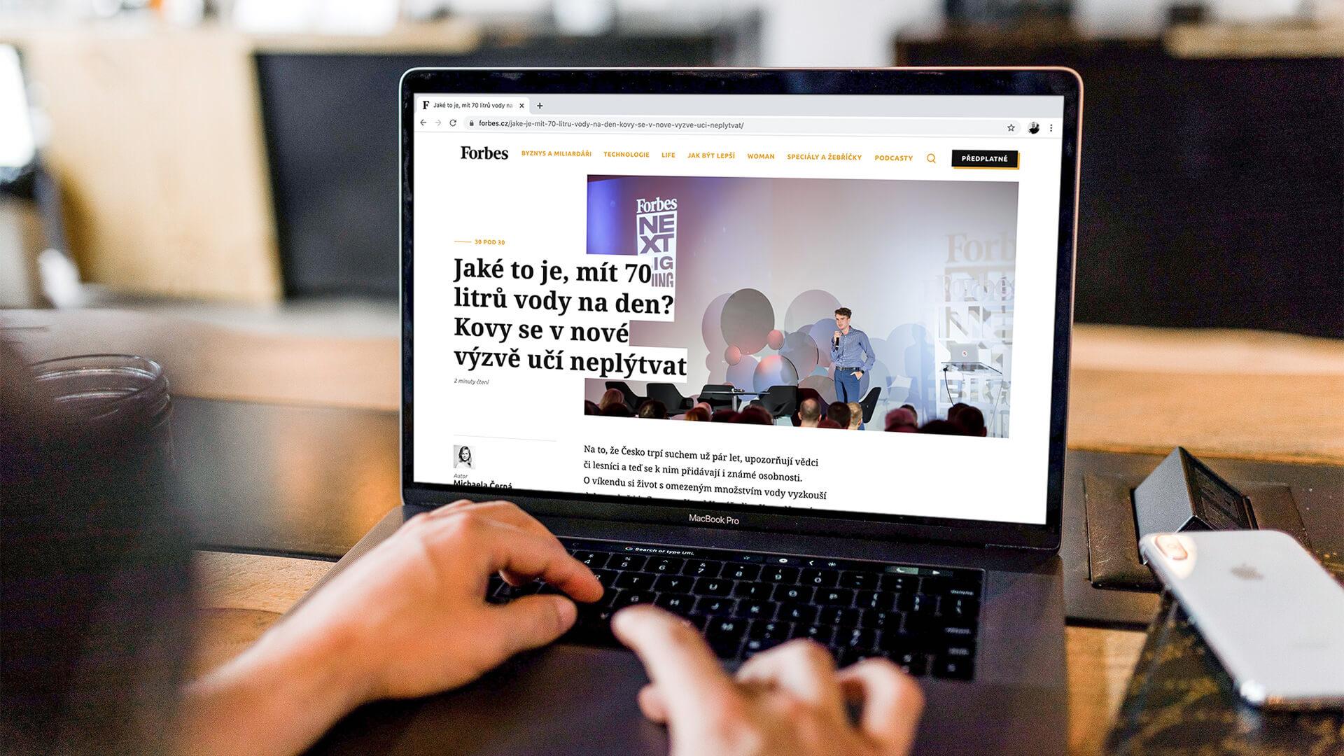 Fotografie počítače, na kterém je otevřená stránka Forbes.cz s článkem o kampani
