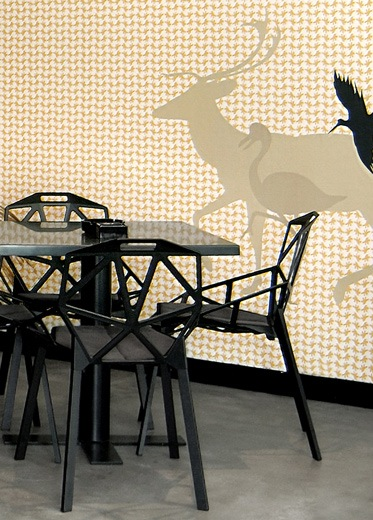 A black custom-made table with Konstantin Grcic chairs, in front of a wallpaper design with animal illustrations.