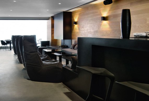 A warm lounge area with wooden wall cladding and a black bar.