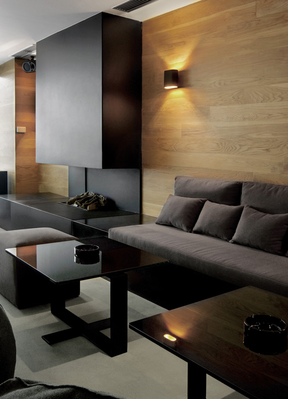 An atmospheric contemporary bar lounge with a black metal fireplace.