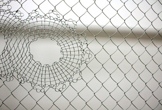 A close-up view of custom-made wire fencing with a floral lace pattern.