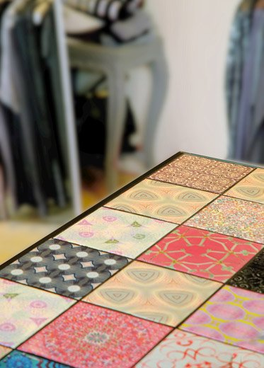 A retail reception counter featuring a colorful assortment of digitally printed fractal tiles.