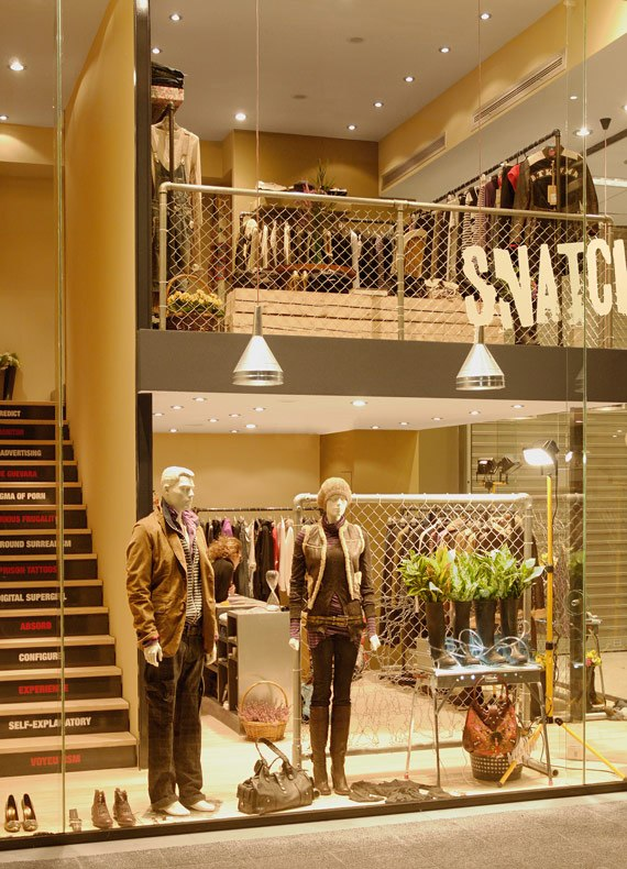 Snatch's facade with floor to ceiling seamless windows revealing its minimal interior and quirky window display.