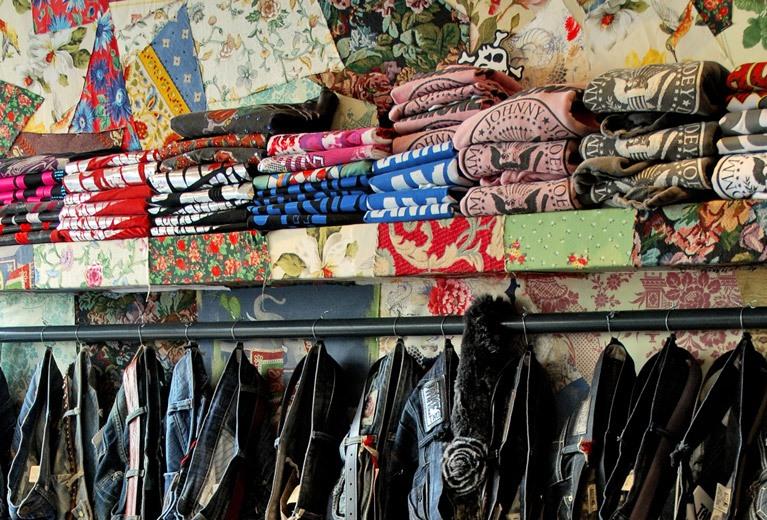 Retail shop display designed using black pipe clothing racks and patchwork shelfs.