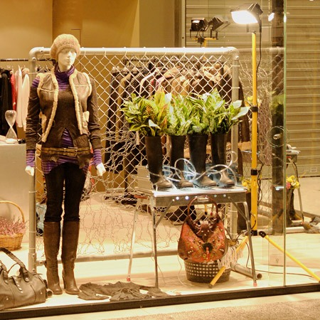 A retail shop window design with a mannequin next to an ephemeral installation of found objects.