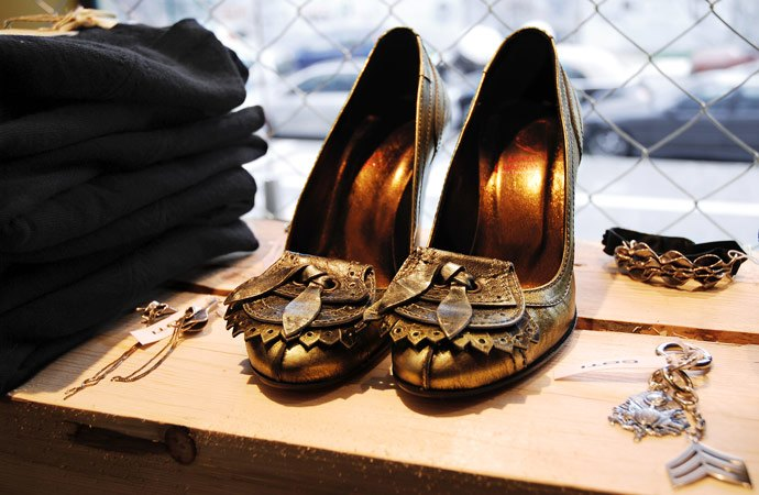 Vintage bronze shoes displayed on a wooden construction beam.