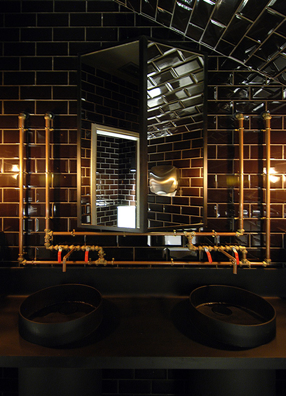 A restaurant bathroom design with an industrial black metal vanity, exposed copper pipe installation and dramatic lighting.