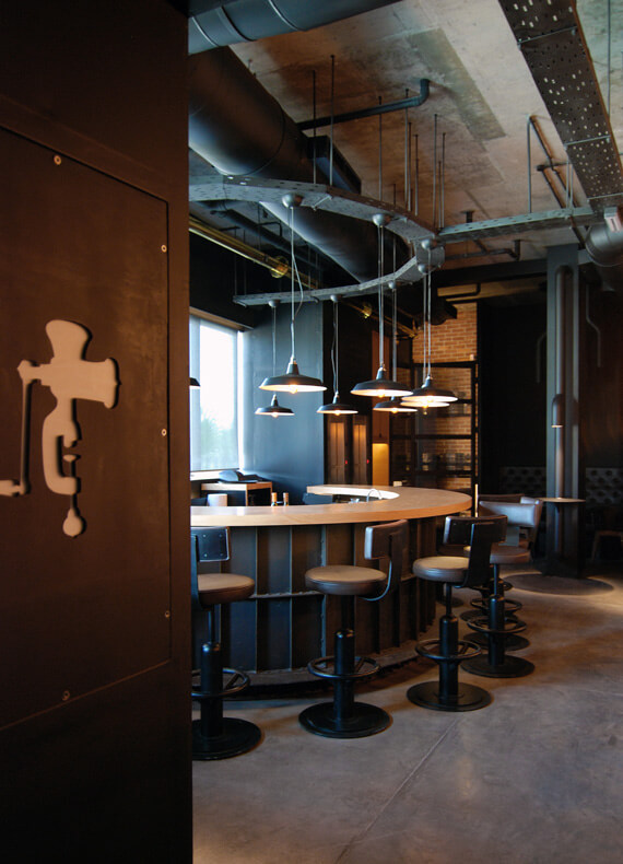 The interior design of an industrial bar featuring exposed beams, brick walls, concrete floors and piston-like bar stools.