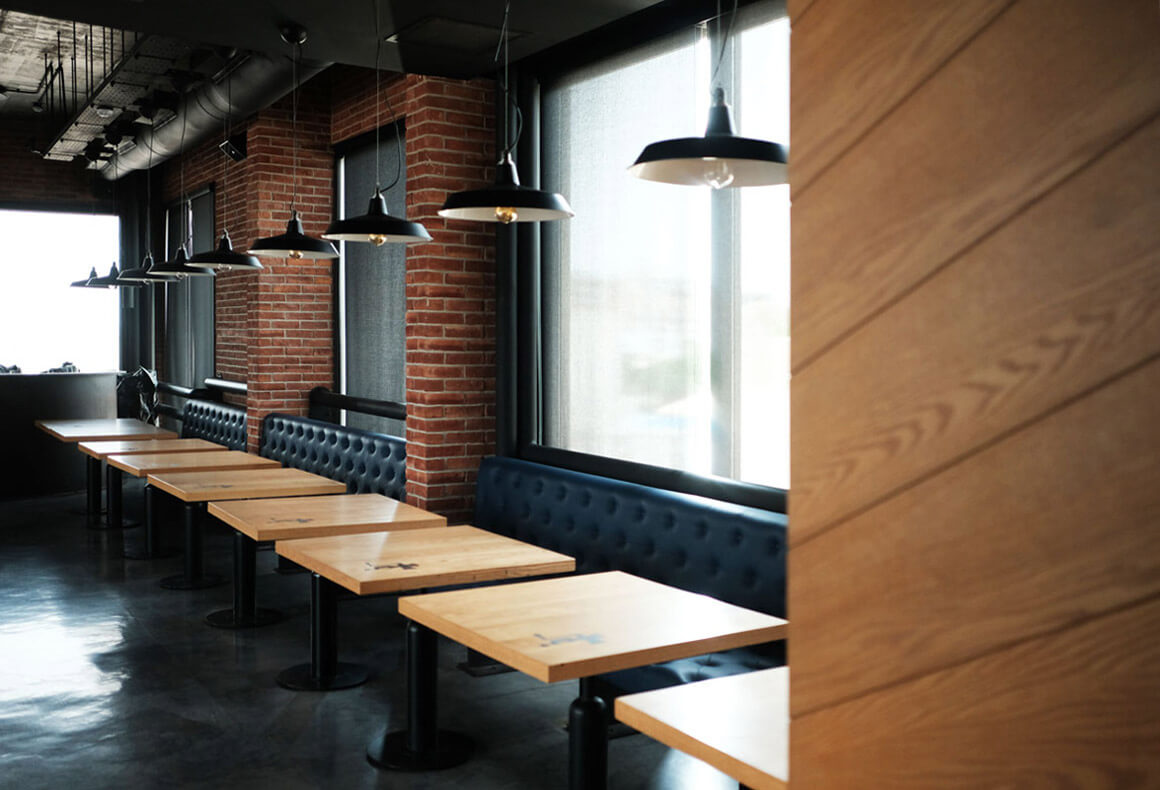 The interior of an industrial chic restaurant showing bespoke oak tables softening the roughness of brick and metal.