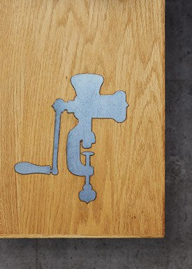 An oak dining table with a cast iron inlay of a traditional handheld meat mincer.