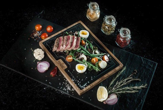 The Foundry's signature seared tuna dish served on a wooden platter with a slate inlay.