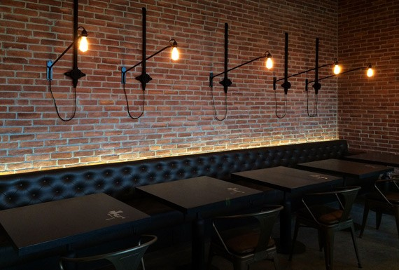 A bar seating area with black leather sofas, black oak tables and industrial wall light fixtures on aged red brick walls.