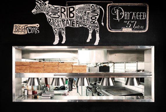 A feature blackboard wall with an opening framed in stainless-steel which looks into the restaurant kitchen.
