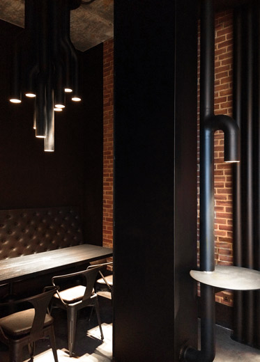 A seating area in a recess which is dramatically lit by a custom-made black steel pipe chandelier.
