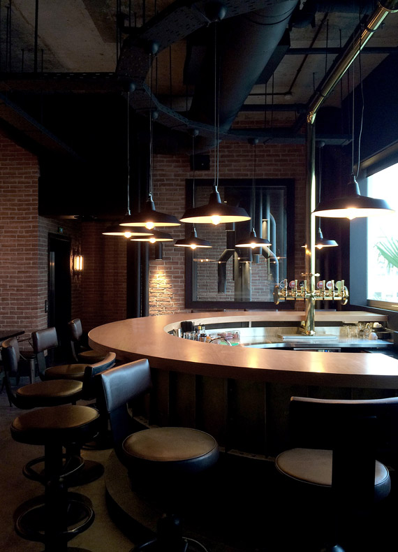 The Foundry bar, with a feature gold pipe running across the ceiling to transport beer from the keg room to the draft tower.